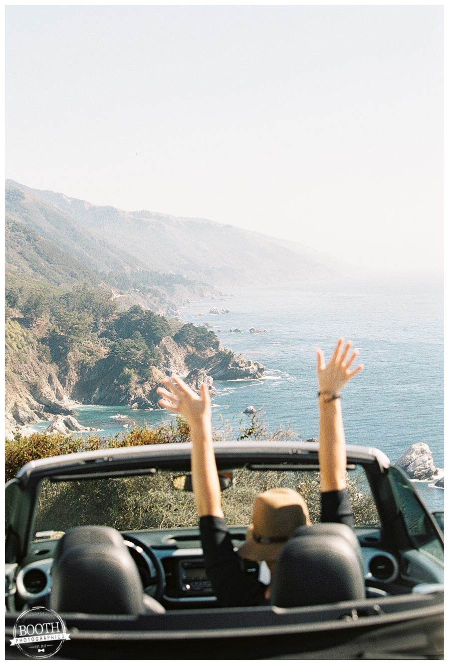 Stephanie throws her hands in the air in our convertible parked along the California coast in Big Sur