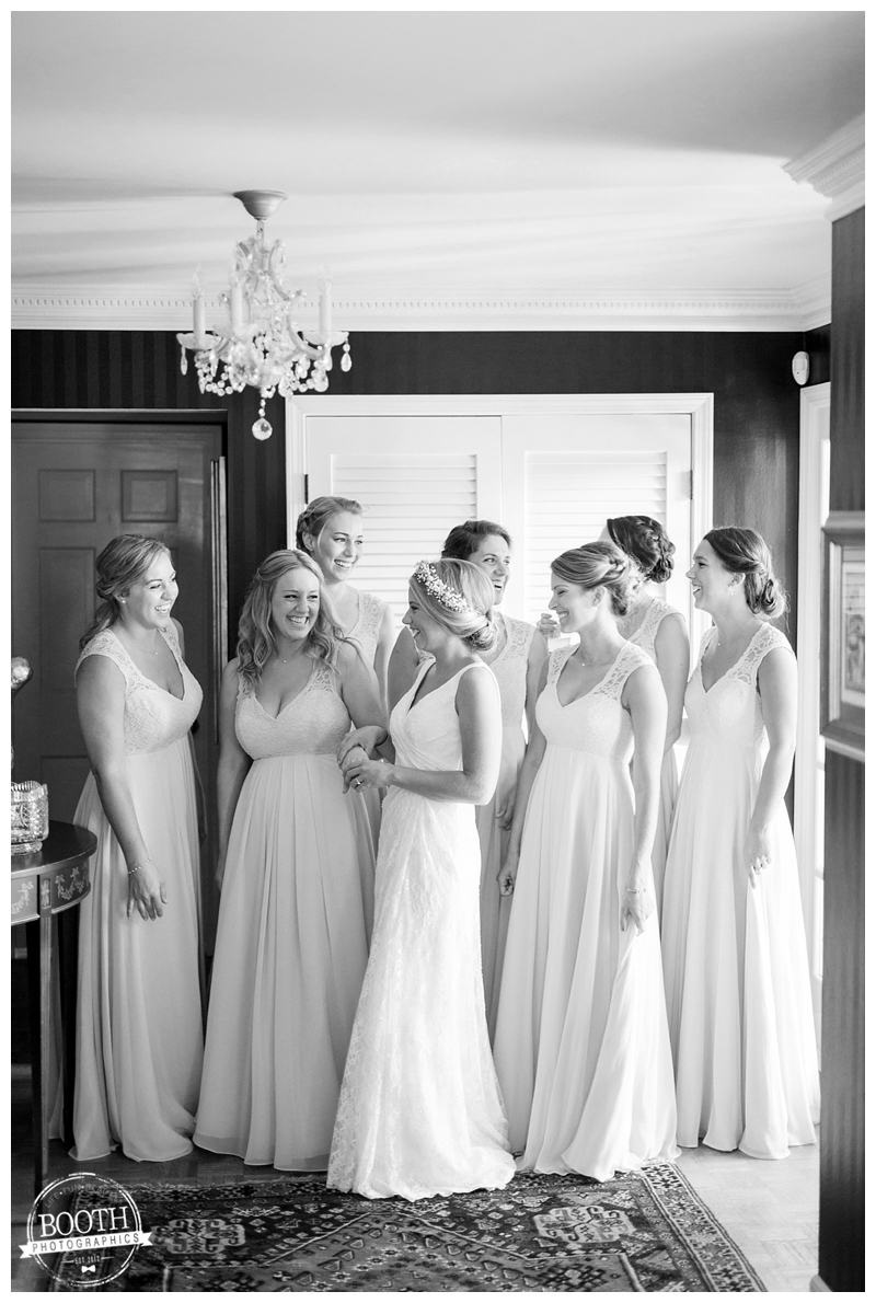 bridesmaids helping a bride get into her dress