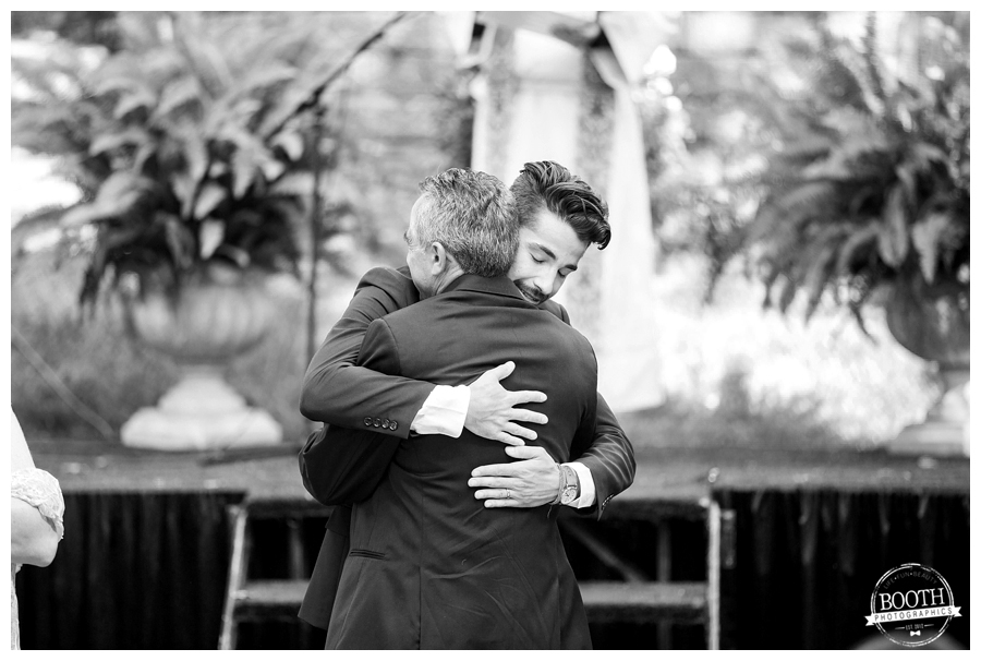 father and son hugging during the wedding ceremony