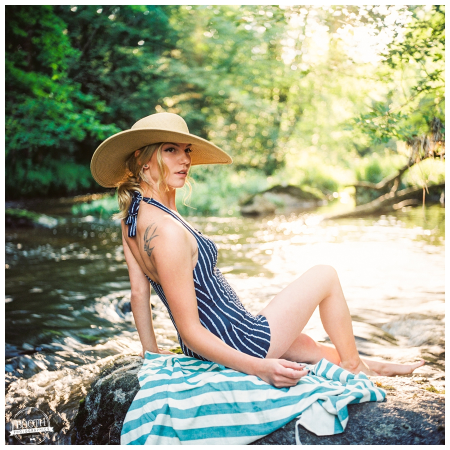 model Jenna Dickson wearing an Anthropologie Bathing suit on a rock in a river in Wausau, WI