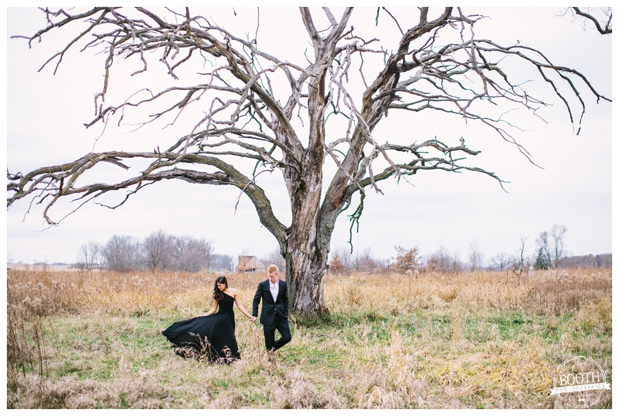 editorial photo of a classy couple walking under a dramatic dead tree