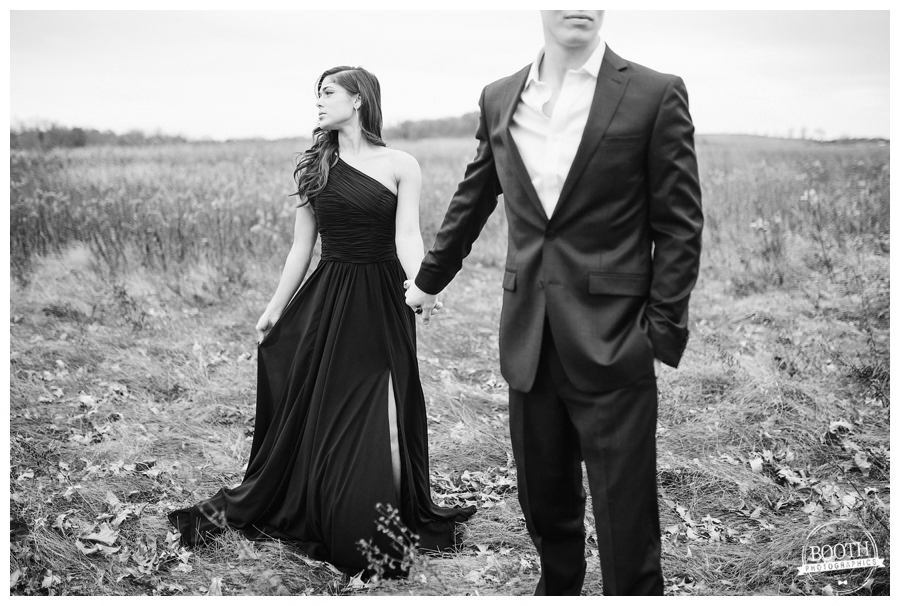 man in a black suit and woman in a black gown holding hans in a field in Governor Nelson State Park in Madison, WI