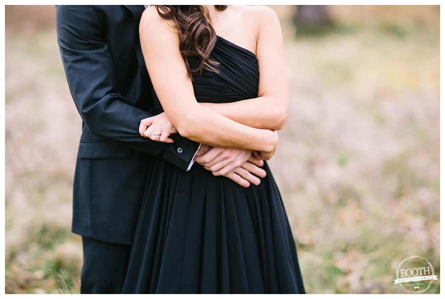 man in a black suit and woman in a black gown embracing in a field in Governor Nelson State Park in Madison, WI