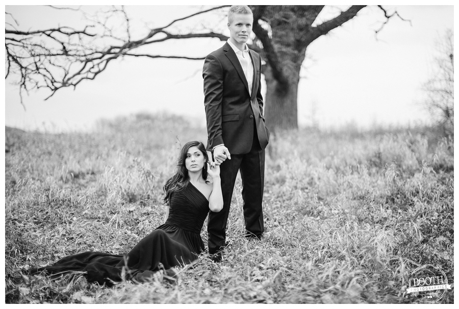 man in a suit and woman in a black ball gown in an editorial pose in a field