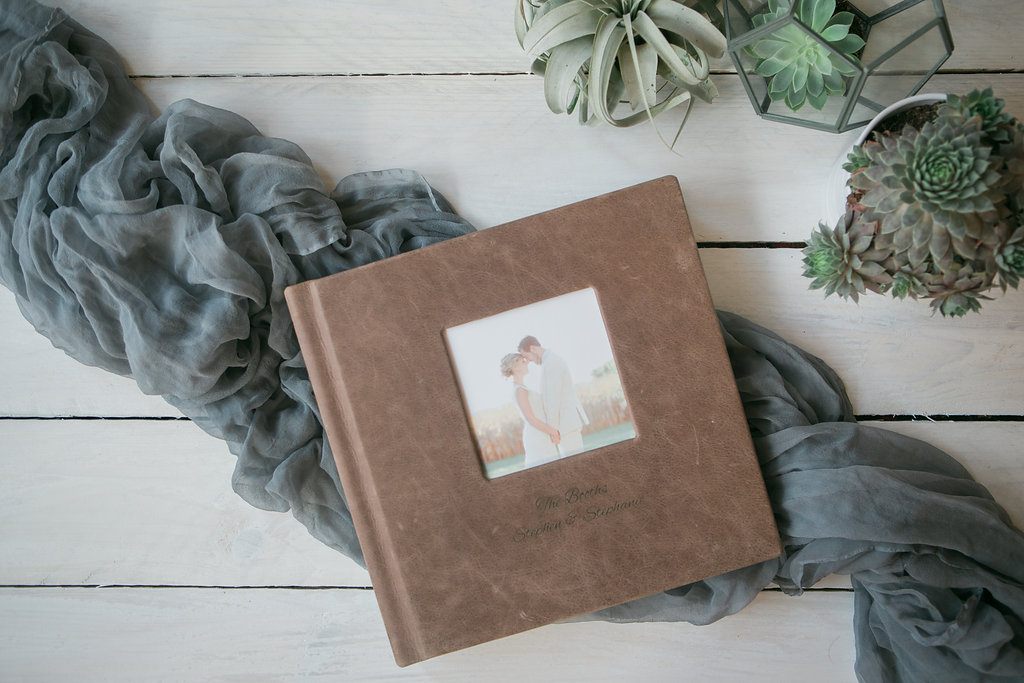 tuscan leather kiss books album on whitewashed coffee table with succulents and air plants