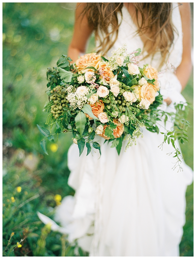 bride holding bouquet of hops and garden roses on mountainside in Durango CO photographed by Booth Photographics, destination fine art wedding photographers