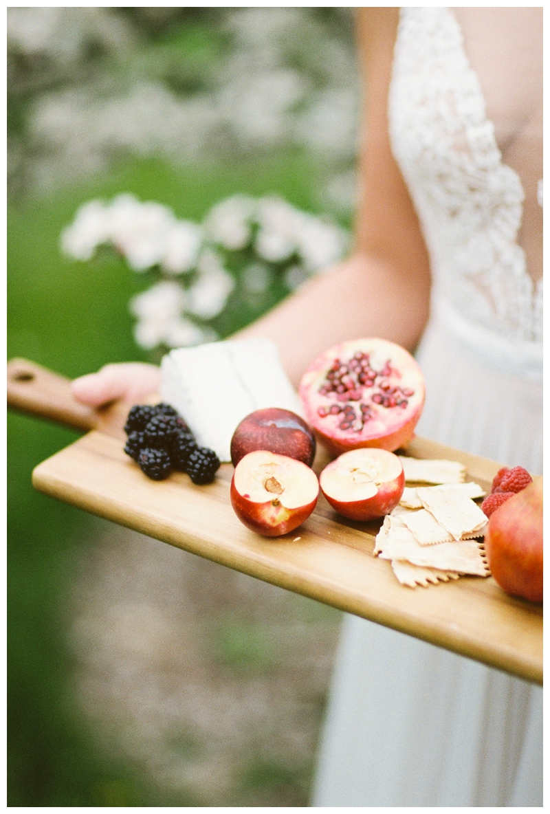 bride holding cheese board in Madison, WI photographed by Booth Photographics, destination fine art wedding photographers