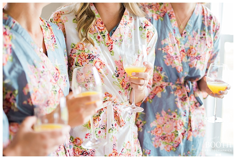 bride and her bridesmaids wearing Plum Pretty Sugar robes drinking mimosas at her rustic outdoor wedding