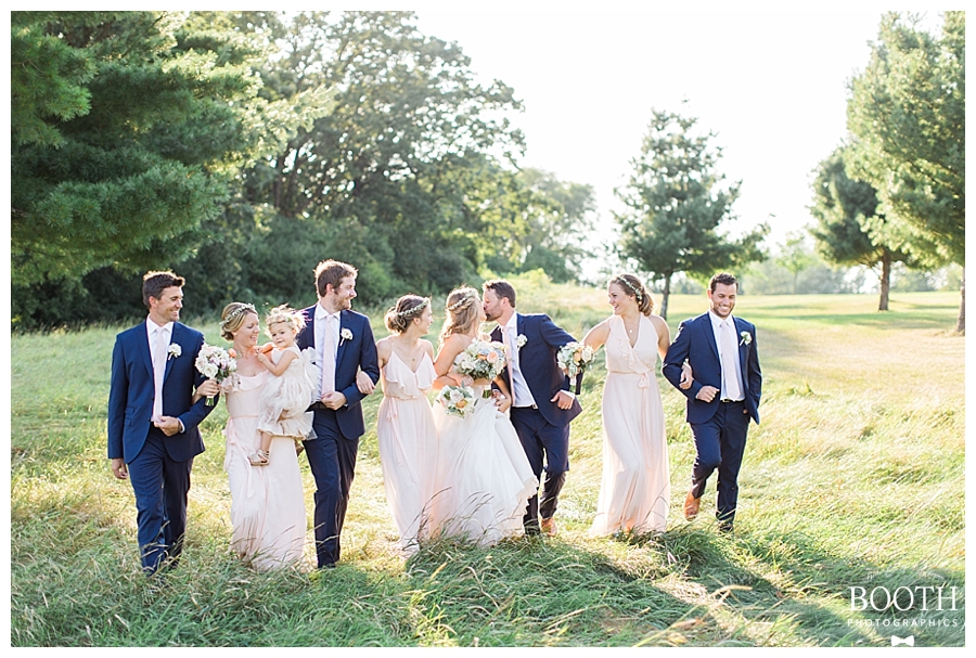 pink and navy bridal party walking through a field at sunset at a rustic outdoor wedding