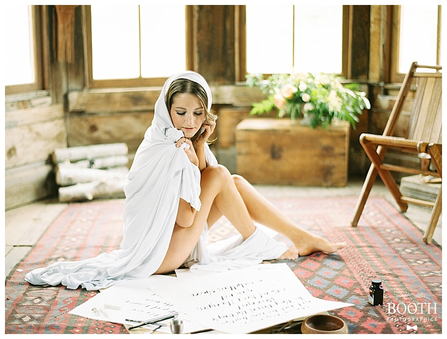 bride sitting on floor wrapped in a sheet painting in her Colorado boudoir session by fine art film photographers, Booth Photographics