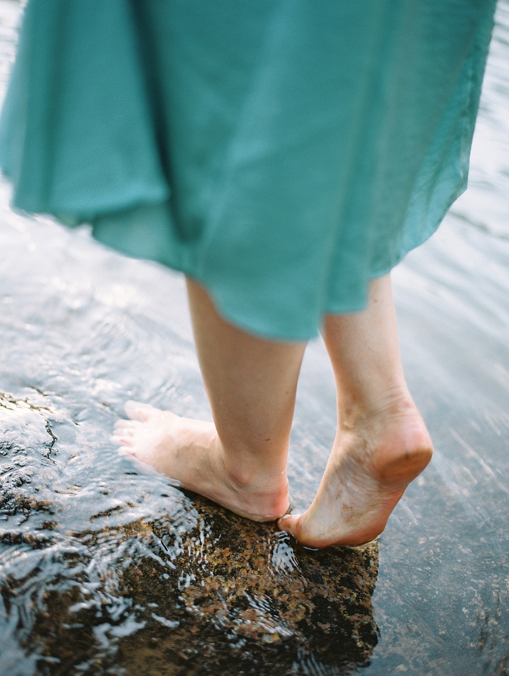 girl standing barefoot in the water