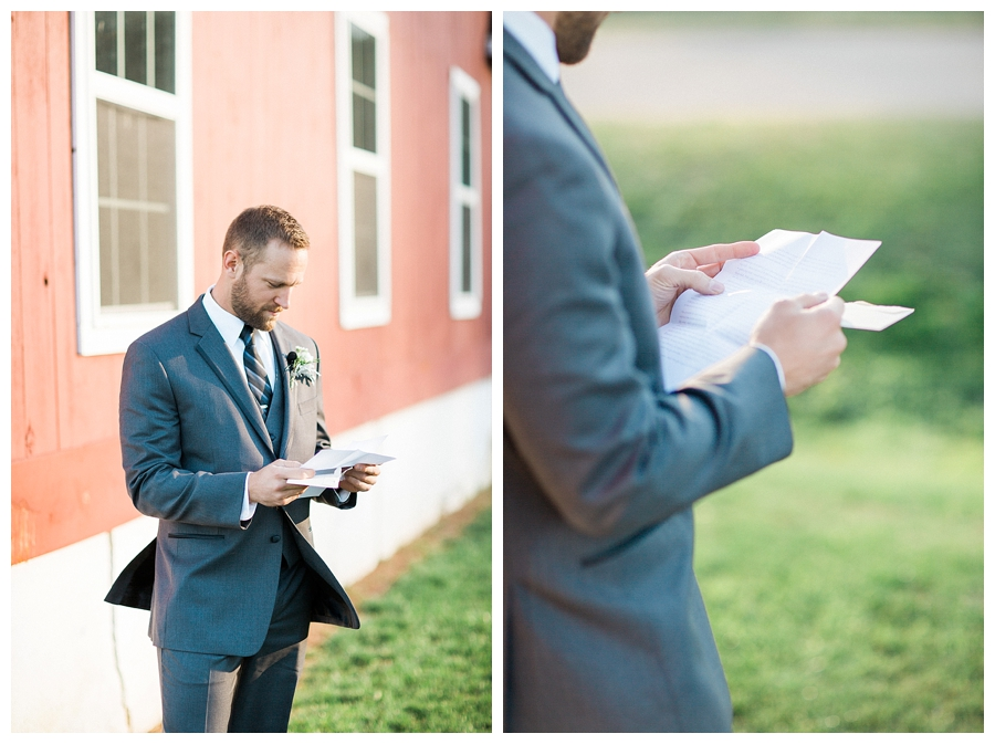 Groom reading a handwritten letter from his bride alongside a barn before their rustic outdoor fall wedding