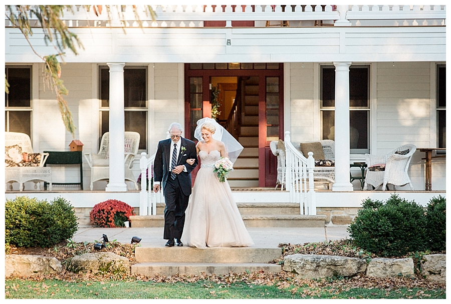 Bride walking the aisle from a rustic farmhouse for her rustic outdoor wedding ceremony at Sugarland Barn