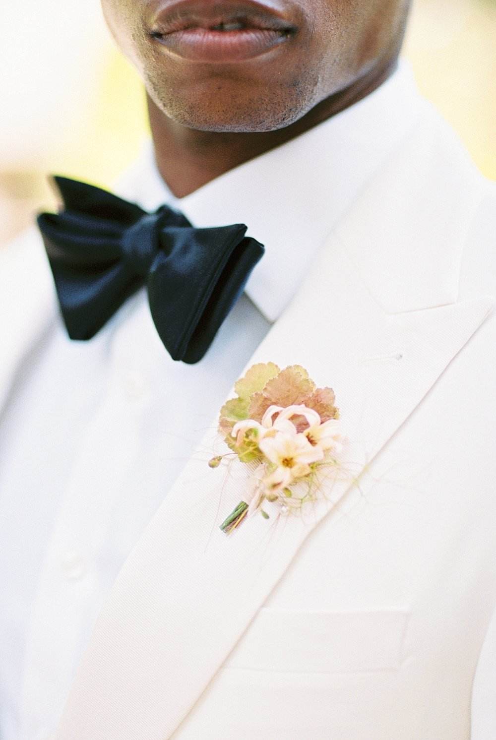 Groom in white dinner jacket from the Black Tux for his wedding at Fenyes Mansion in Pasadena, California
