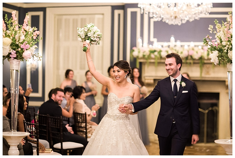 Bride and groom walking back down the aisle during their classic and romantic fireplace wedding ceremony at the Madison Club