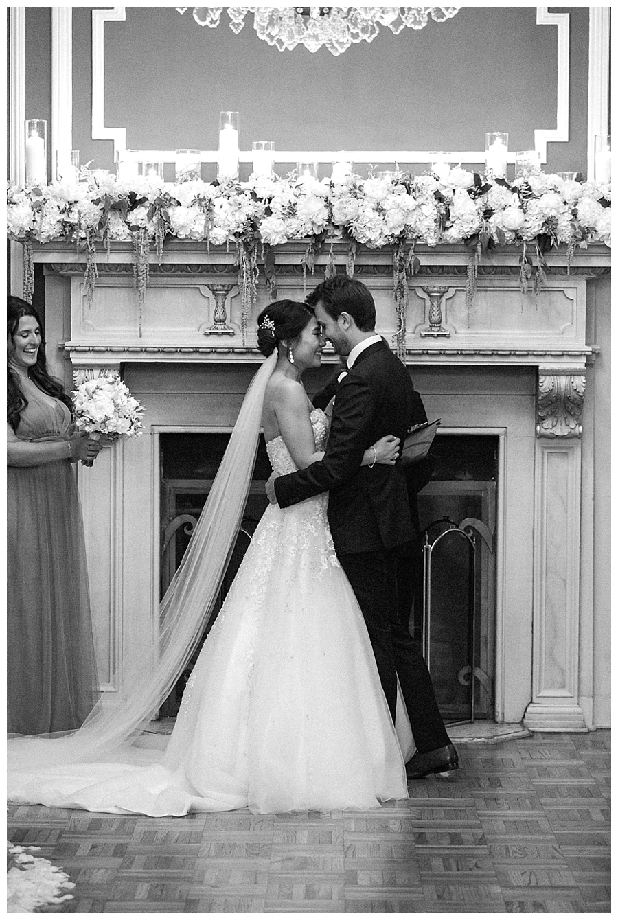 Bride and groom sharing first kiss during their classic and romantic fireplace wedding ceremony at the Madison Club