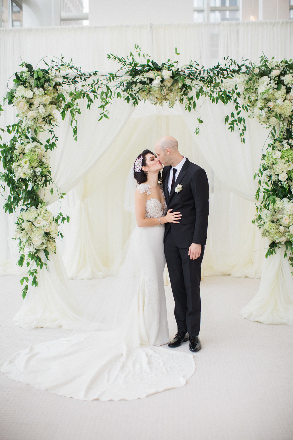 Bride and groom kissing under an all white and greenery floral chuppah