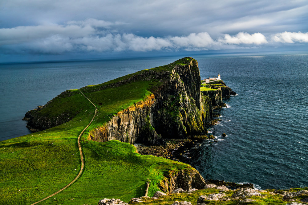 The beautiful Neist Point Lighthouse, the most famous scene on Isle of Skye. The little white specks you see on the grass are sheep.