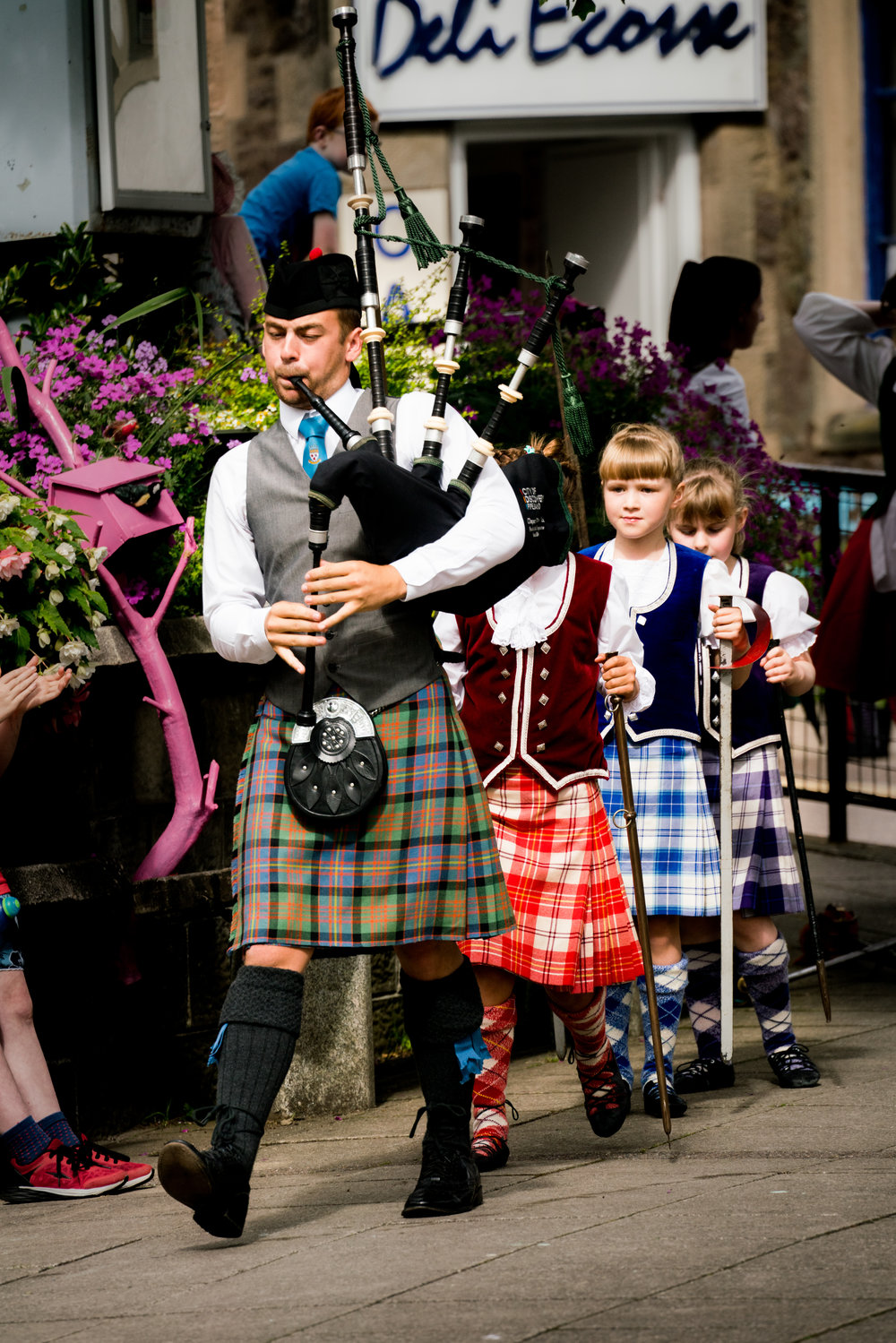 Scottish bagpiper and kilt-wearing girl dancers marching out to perform a sword dance