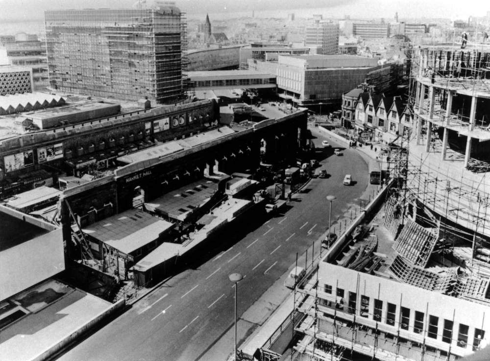 Old Birmingham is disappearing as the new Birmingham rises up in the early 1960s. On the left is what is left of the old Market Hall and behind it the Bull Ring Centre is emerging. The middle is dominated by the new Smallbrook Queensway and on the right the Rotunda is in the throes of construction.