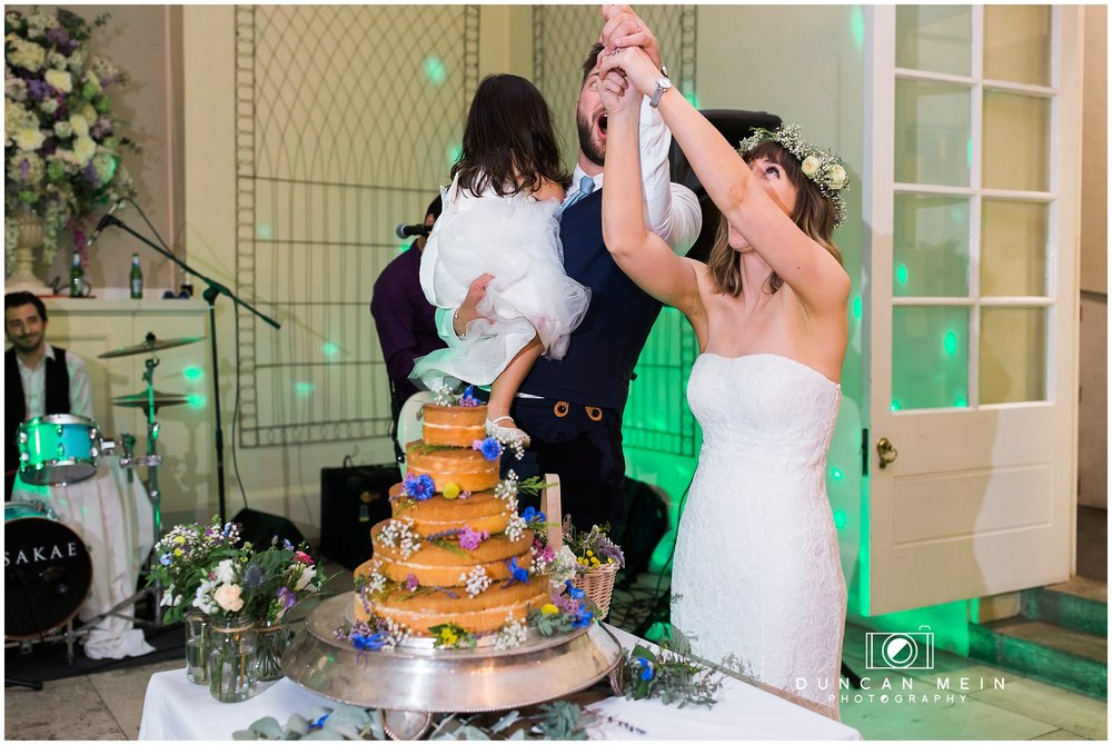 Wedding at Goldney Hall - Bride and Groom cutting the cake
