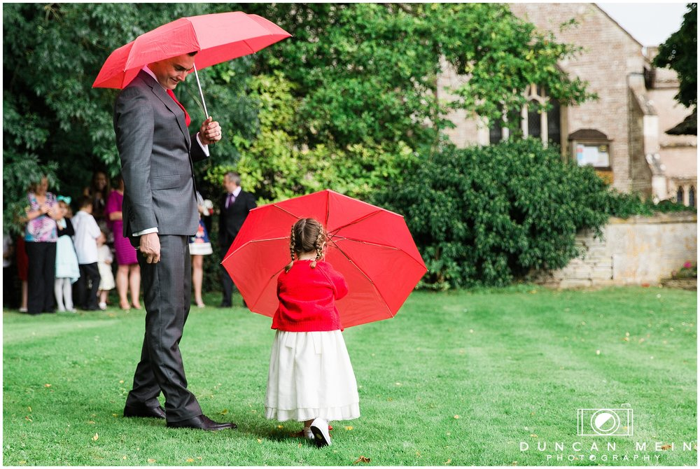 Wedding in Crudwell Village - Groom and Flowergirl in the rain
