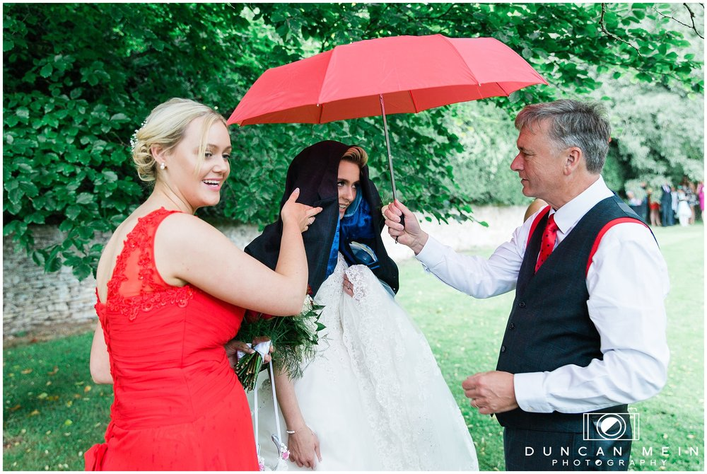 Wedding in Crudwell Village - Bride sheltering from the rain