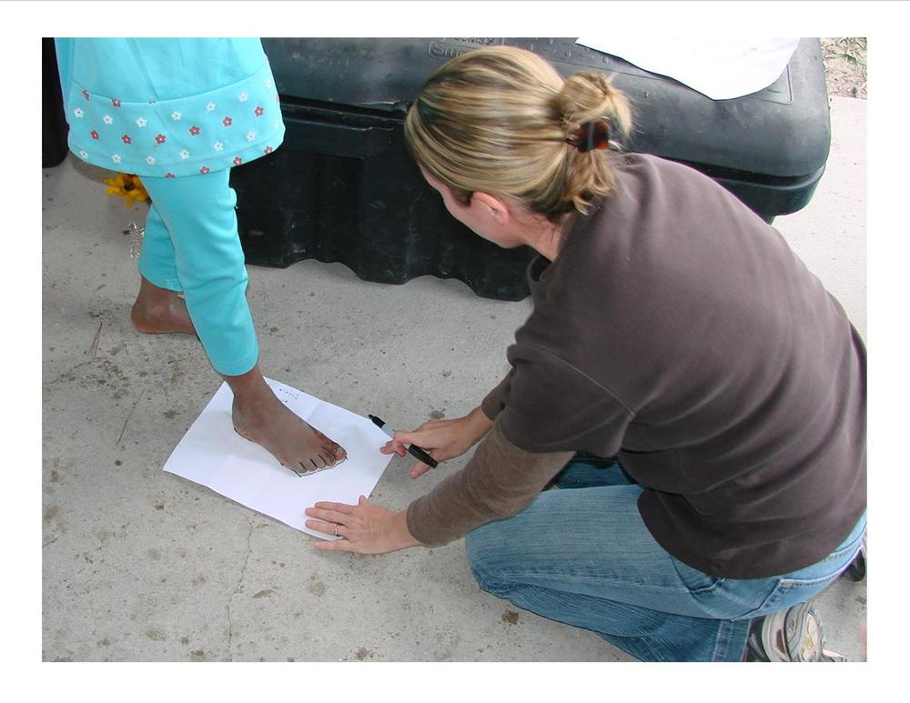 Our founder and missionary, Robyn Breaux, tracing the feet of the children so ER International could buy them shoes
