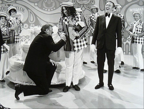 John Wayne and Tiny Tim helped Laugh-In celebrate its 100th episode in 1971. Co-host Dan Rowan yucks it up in his tuxedo.