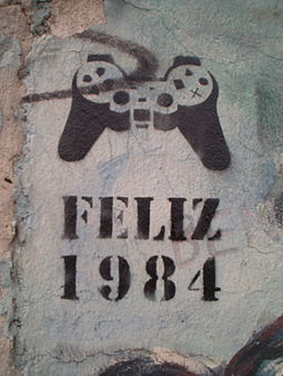"""""""Happy 1984"""" (in Spanish) stencil graffito, denoting  mind control via a video game controller, on a standing piece of the  Berlin Wall , 2005."""