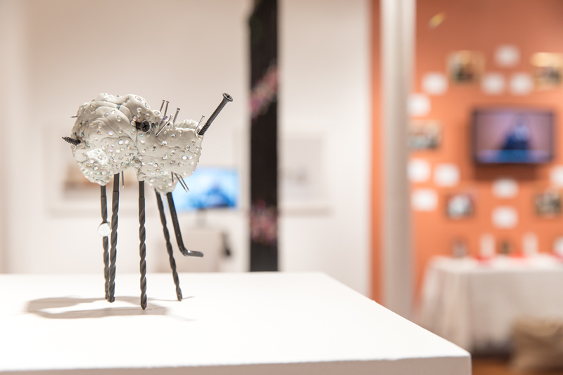 """""""What Can Siri Answer?'' (epoxy clay. rhinestones, screw, nail, L-shaped key wrench and barrel nut!), by Heesun Shin, in the nine-woman show """"Up-Root,'' at Periphery Space Gallery, Providence, through Nov. 18. The gallery says:    """"Nine women artists speak to their individual cultural backgrounds. ...Many of the works are installations and even with nine artists the work is so tightly curated that they speak to each other. There is a strong narrative running through each artists body of work that speaks to traditions and belief systems one is brought up with or introduced to later. The show is very tactile ....'    Further, """"Becoming American is often accompanied by a process of assimilation, particularly for second-generation immigrants, when a need to feel connected in a new community causes some to abandon ancestral traditions. At a time of cultural unrest and spiritual disconnection in America, this exhibition presents artists who embody, perpetuate and reclaim the cultures,  ceremonies  and rituals of their ancestors as a strategy for wholeness.''"""