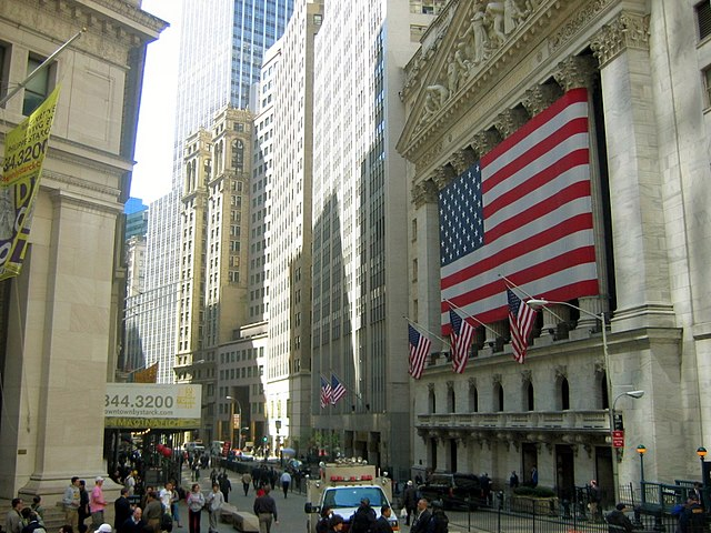 Wall Street, with the flag-bedecked New York Stock Exchange.