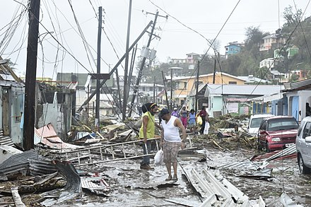 A road in the  Roseau area of Puerto Rico littered with structural debris, damaged vegetation and downed power poles and lines after Maria blows through.