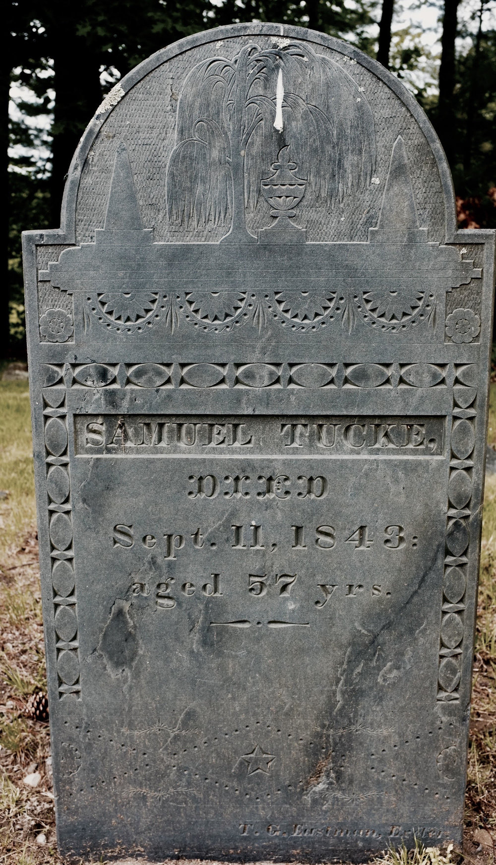 Samuel Tucke's stone of 1843 is of slate, the stonecutter's name is inscribed at the bottom and the urn and weeping willow motifs are more sophisticated than the primitive winged head of the early stones.
