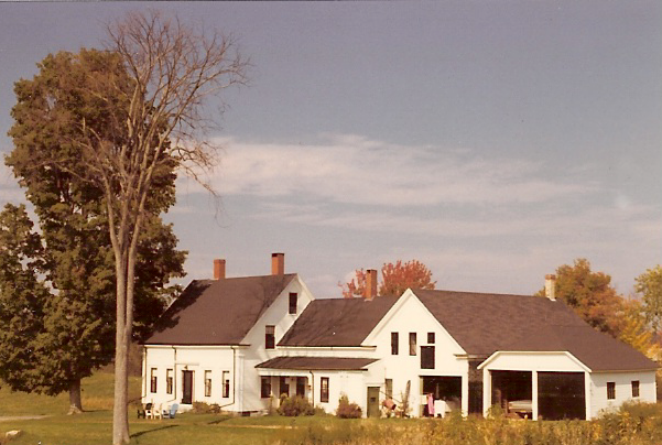 """A """"connected farmhouse'' in  Windham, Maine . The barn dates from the late 18th Century. The house itself was built in three stages during the 19th Century while the unconnected garage was a 20th-Century addition. All doors of the structure are visible in this view from the south side, where sun would melt accumulated snow and ice. Following the 20th-Century outbreak of  Dutch elm disease only one  American elm remains of the line that provided summer shade along the southern and western sides of the building."""