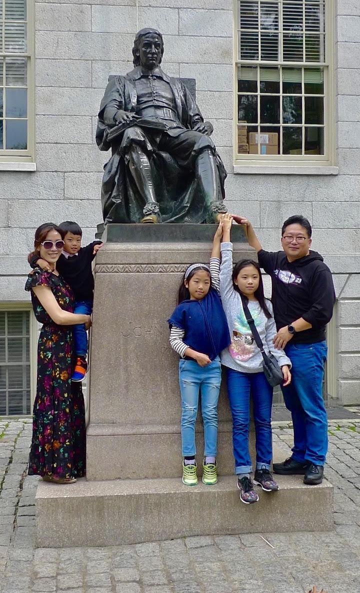 Family at the statute of Harvard benefactor John Harvard (1607-1638) in Harvard Yard.    — Photo by William Morgan