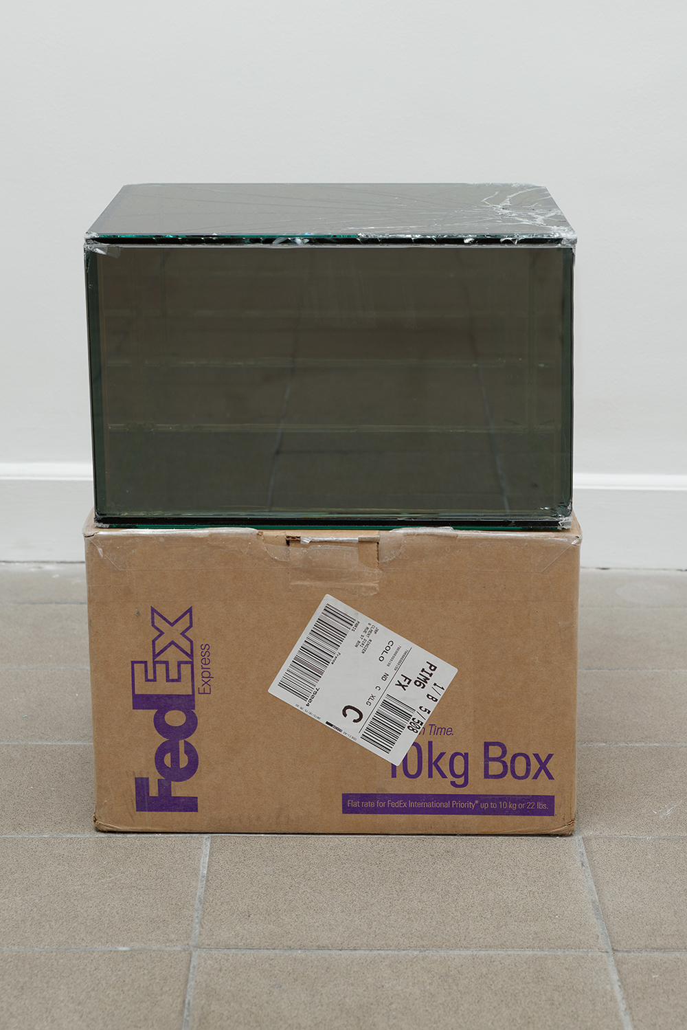 FedEx® 10kg Box  © 2006 FedEx 149801 REV 9/06 MP, International Priority, Los Angeles-Paris trk#796907687919, Los Angeles-Paris, October 14-16, 2013    2013–   Laminated Mirropane, FedEx shipping box, accrued FedEx shipping and tracking labels, silicone, metal, tape  10 1/2 x 16 1/4 x 13 1/4 inches   FedEx Glass Works, 2007–