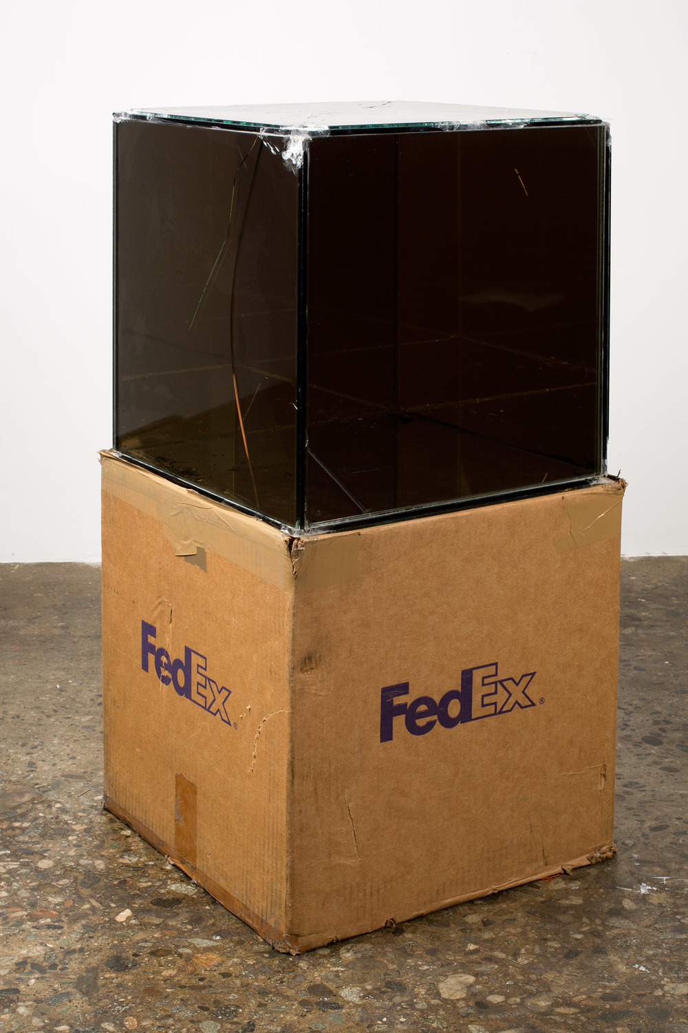 FedEx® Kraft Box  © 2005 FEDEX 330504 10/05 SSCC, Priority Overnight, Los Angeles–Miami trk#865344981303, October 29–30, 2008, Priority Overnight, Miami–Ann Arbor trk#861049125148, March 3–4, 2009, Standard Overnight, Ann Arbor–Los Angeles trk#868274625716, July 9–10, 2009, Standard Overnight, Los Angeles–New York trk# 774901718297, November 4–5, 2015, Standard Overnight, New York–Los Angeles trk#775241156204, December 21–22, 2015    2008–   Laminated Mirropane, FedEx shipping box, accrued FedEx shipping and tracking labels, silicone, metal, tape  16 x 16 x 16 inches   FedEx Glass Works, 2007–
