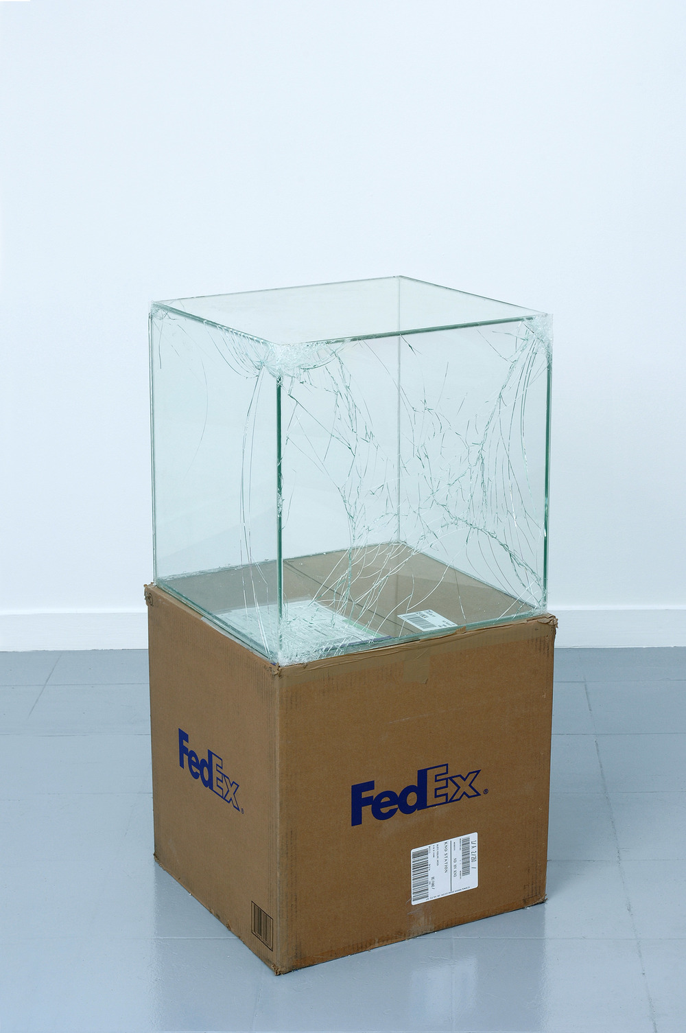 FedEx® Large Kraft Box  © 2005 FEDEX 330508 REV 10/05 SSCC, International Priority, Los Angeles–Brussels trk#865282057964, October 27–30, 2008, International Priority, Brussels–Los Angeles trk#866071746385, Janurary 8–9, 2009, Standard Overnight, Los Angeles–New York trk#872632033108, April 29–30, 2010, Standard Overnight, New York–Los Angeles trk#796210730703, September 2–3, 2010, Priority Overnight, Los Angeles–New York trk#794583197877, March 28–29, 2011, Priority Overnight, New York–Los Angeles trk#611849858596, January 13–14, 2015    2008–   Laminated glass, FedEx shipping box, accrued FedEx shipping and tracking labels, silicone, metal, and tape  20 x 20 x 20 inches   Industrial Pictures, 2008