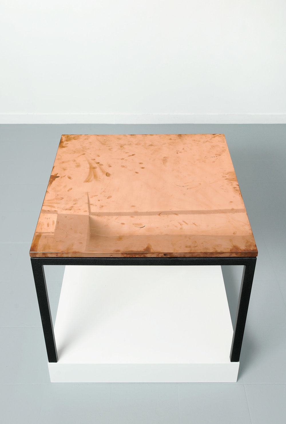 Copper Surrogate (Table: designed by Charlotte Perriand and Le Corbusier, 1959; Galerie Rodolphe Janssen, Brussels, Belgium, August 10th–September 2nd, 2011)   2011  Polished copper table top and powder-coat steel  Table: 33 5/8 x 33 5/8 x 1 inches   Surrogates (Tabletop and Desktop), 2008–    Diapositives, 2011
