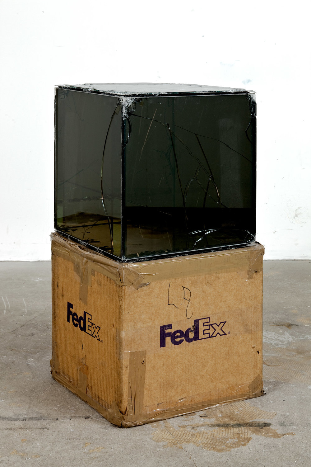 FedEx® Kraft Box  © 2005 FEDEX 330504 10/05 SSCC, Priority Overnight, Los Angeles–Miami trk#865344981314, October 29–30, 2008, Priority Overnight, Miami–Los Angeles trk#861049125089, November 17–18, 2008, Priority Overnight, Los Angeles-Miami Beach trk#860147611241, December 01–02, 2008, Priority Overnight, Miami–Los Angeles trk#867525901310, December 08–09, 2008, Priority Overnight, Los Angeles–Ann Arbor trk#867525901228, March 09–10, 2009, Standard Overnight, Ann Arbor–Los Angeles trk#868274625705, July 09–10, 2009, Standard Overnight, Los Angeles–San Francisco trk#870069766460, August 27–28, 2009, Standard Overnight, San Francisco–Los Angeles trk#870342520112, November 12–13, 2009   2008  Laminated Mirropane, FedEx shipping box, accrued FedEx shipping and tracking labels, silicone, metal, and tape  16 x 16 x 16 inches   FedEx Glass Works, 2007–    Pulleys, Cogwheels, Mirrors, and Windows, 2009