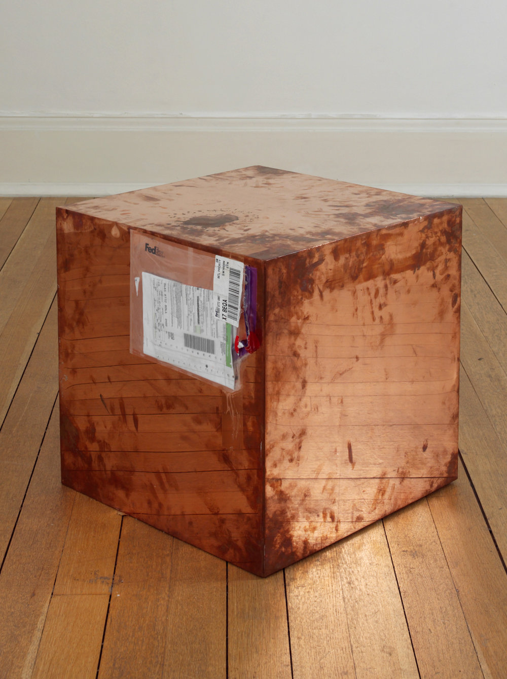 FedEx® Large Kraft Box  © 2005 FEDEX 330508 REV 10/05 SSCC, International Priority, Los Angeles–London trk#868587728061, October 2–5, 2009, International Priority, London–Zurich trk#863822956490, November 26–December 2, 2009    2009–   Polished copper, accrued FedEx shipping and tracking labels  20 x 20 x 20 inches   Production Stills, 2009