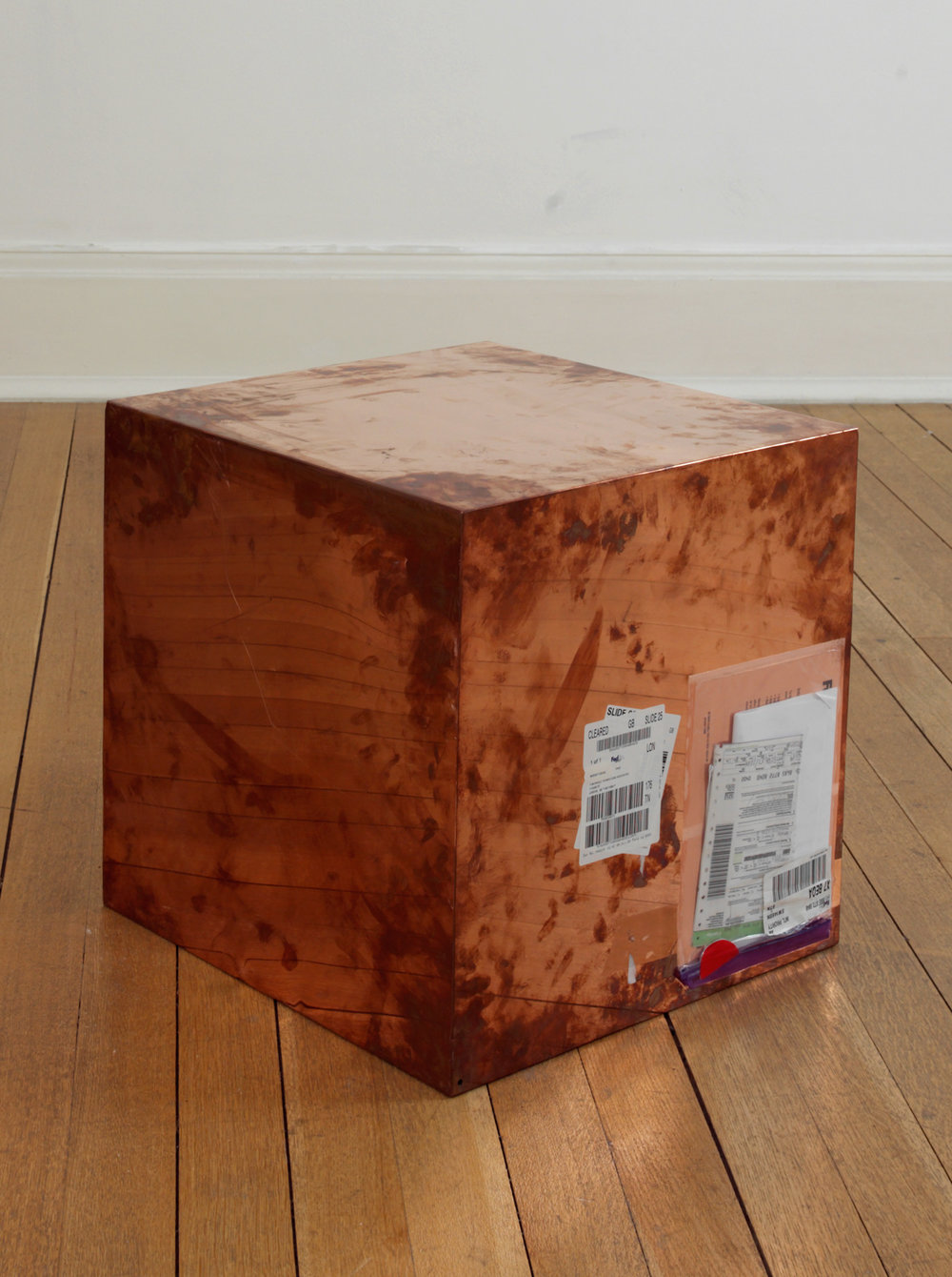 FedEx® Large Kraft Box  © 2005 FEDEX 330508 REV 10/05 SSCC, International Priority, Los Angeles–London trk#868587728040, October 02–05, 2009, International Priority, London–New York trk#863822956489, November 18–20, 2009, International Priority, New York–London trk#795200981790, September 19–21, 2011    2009–   Polished copper, accrued FedEx shipping and tracking labels  20 x 20 x 20 inches   Production Stills, 2009