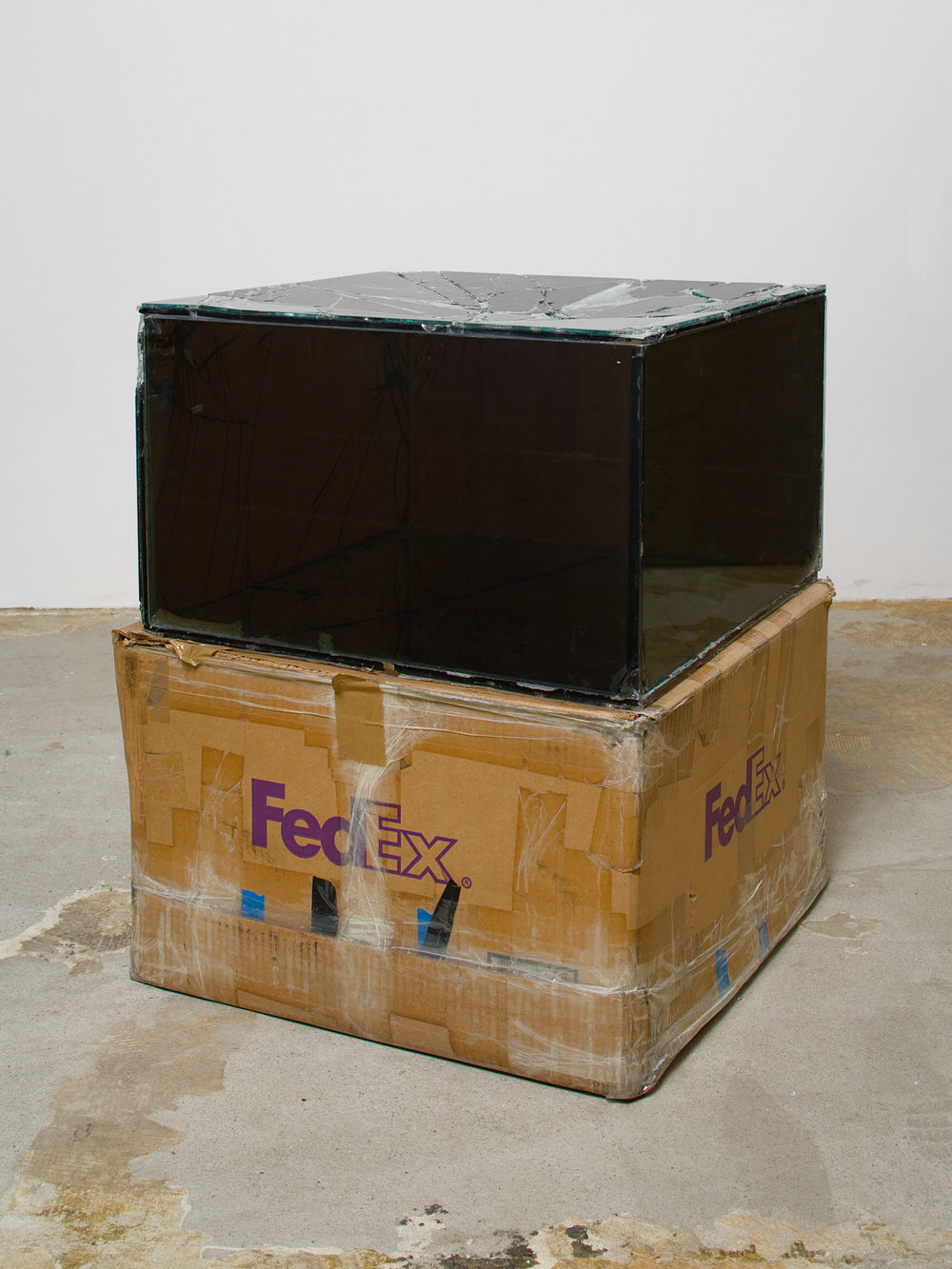 Fedex® Medium Kraft Boxes, Priority Overnight, Los Angeles–New York trk#864049582968 & trk#867525901423, December 7–10, Priority Overnight, New York–Los Angeles trk#863133194810 & trk#863133194800, December 10–12, 2007, International Priority, Los Angeles–Oostende trk#867279774962 & trk#867279774973, February 9–12, 2009, International Priority, Oostende–Paris trk#803074770903    2007–   Laminated glass, FedEx shipping box, accrued FedEx shipping and tracking labels, silicone, metal, tape  20 x 48 x 20 inches   Science Concrète, 2008