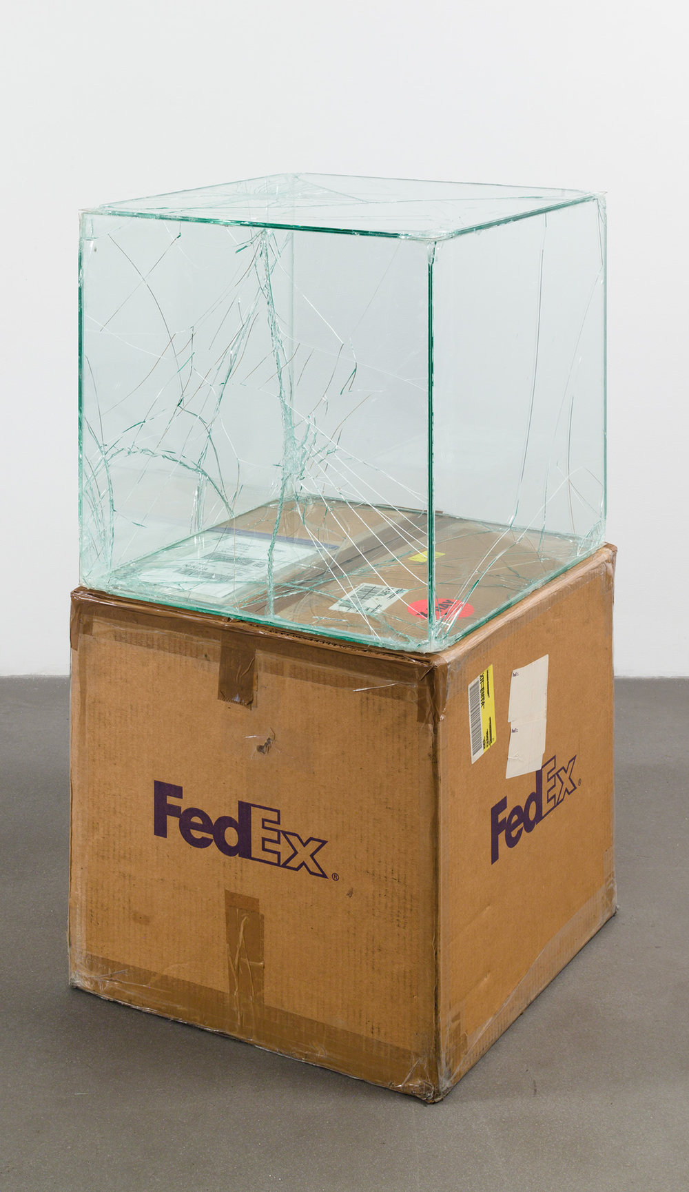 FedEx® Large Kraft Box  © 2005 FEDEX 330508 REV 10/05 SSCC, International Priority, Los Angeles–Brussels trk#865282057975, October 27–30, 2008, International Priority, Brussels–Los Angeles trk#866071746396, December 8–9, 2008, Standard Overnight, Los Angeles–New York trk#774901659423, November 4–5, 2015, Standard Overnight, New York–Los Angeles trk#775241449093, December 21–22, 2015    2008–   Laminated glass, FedEx shipping box, accrued FedEx shipping and tracking labels, silicone, metal, tape  20 x 20 x 20 inches   Industrial Pictures, 2008    Great Hall Exhibition, 2015
