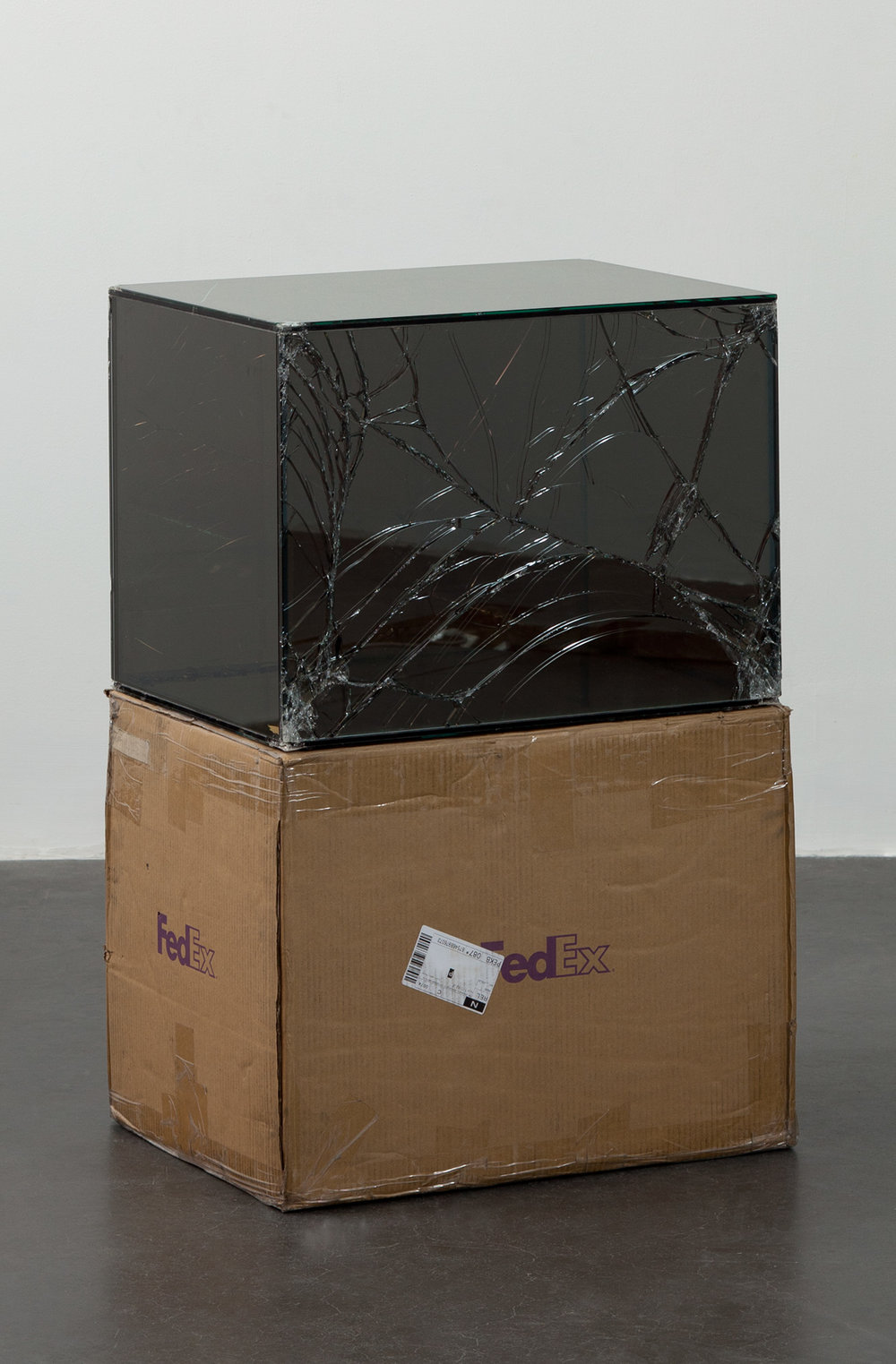 FedEx® Large Kraft Box  © 2004 FEDEX 155143 REV 10/04 SSCC, International Priority, Los Angeles–Beijing trk#875468976073, September 09–14, 2011, International Priority, Beijing–Miami trk#874108926322, November 23–28, 2011, International Priority, Los Angeles–London trk#793287180666, February 29–March 2, 2012    2011–   Laminated Mirropane, FedEx shipping box, accrued FedEx shipping and tracking labels, silicone, metal, tape  23 5/8 x 18 1/2 x 18 1/2 inches   Securities and Exchanges, 2011