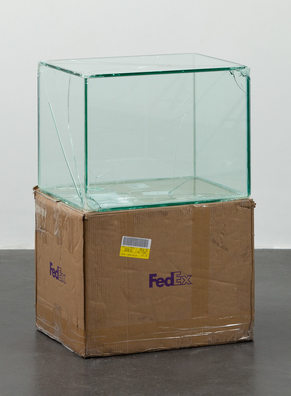 FedEx® Large Kraft Box  © 2004 FEDEX 155143 REV 10/04 SSCC, International Priority, Los Angeles-Beijing trk#875468976062, September 9–14, 2011, International Priority, Bejing–London trk#874594463978, March 13–15, 2012    2011–   Laminated glass, FedEx shipping box, accrued FedEx shipping and tracking labels, silicone, metal, tape  23 5/8 x 18 1/2 x 18 1/2 inches   Securities and Exchanges, 2011