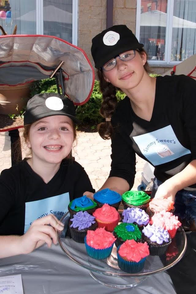 11 year old Samantha Cohen (Standing) and her friend sell cupcakes at Samantha's successful cupcake stand, Sammy Sweet's.