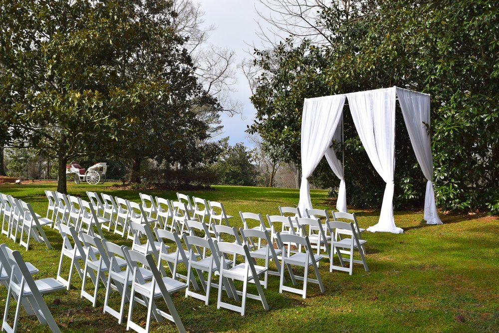 The Lawn  - If you want a natural backdrop and a fully outdoor reception, our rustic and heavy wood arbor is a perfect set up to drape or cover with flowers, seating arrangements are on a well manicured lawn. Guests can move from this space into another location for further celebrating.