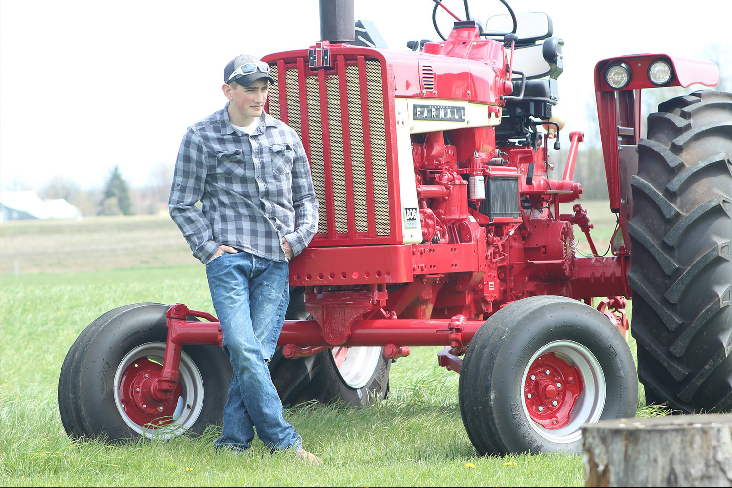 picture of a farmer standing beside a tractor